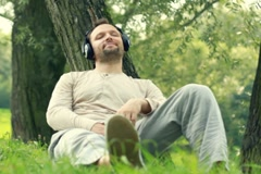 Man with headphones listen to the music by the tree, dolly shot NTSC Stock Footage