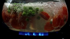 Peas and carrot slices being cooked in hot water - stock footage