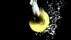 Lemons falling into water (black background) - stock footage