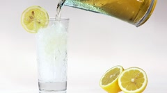 Pouring apple juice into glass of crushed ice with slice of lemon Stock Footage