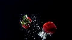 Strawberries floating in water (black background) Stock Footage