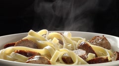 Ladling tomato sauce over ribbon pasta with sliced sausages Stock Footage