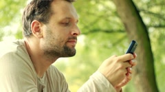 Happy young man sending sms, texting in the park HD Stock Footage
