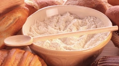 A bowl of flour, various types of bread and bread rolls Stock Footage