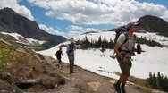 Hikers crossing a high mountain pass extreme Stock Footage