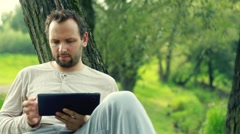 Young happy man with tablet computer by the tree in park HD Stock Footage