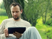 Young happy man with tablet computer by the tree in park NTSC Stock Footage