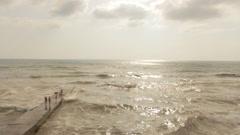 People Walking on the Rock Pier. Stormy Sea. Stock Footage