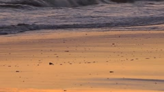 Peaceful beach detail at sunset with waves lapping at the sand Stock Footage