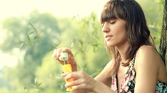 Young attractive brunette blowing bubbles in the park, slow motion HD Stock Footage