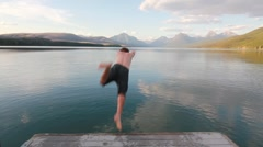 Man diving into lake with mountain view dolly slider Stock Footage
