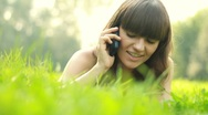 Young woman talking on mobile phone while lying on grass, dolly shot HD Stock Footage