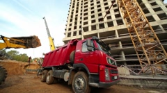 Excavator loads truck at construction site of living house Stock Footage