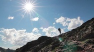 Stock Video Footage of Hiker silhouette climbing to top with sun