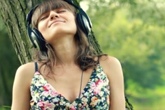 Woman with headphones listen to the music in the park NTSC Stock Footage