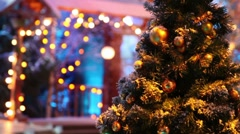Christmas tree with balls stand in front of blurred house - stock footage