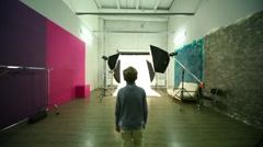 Boy walk across photo studio among spotlights Stock Footage