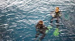 Divers float on water surface in swimming pool Stock Footage