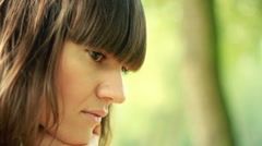 Young, sad, lonely beautiful woman face in the park HD - stock footage