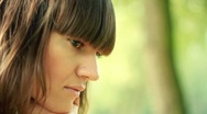 Young, sad, lonely beautiful woman face in the park HD Stock Footage