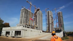 Tall buildings under construction with cranes against sky Stock Footage