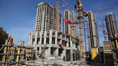 Builder works in front of many tall buildings under construction Stock Footage