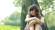 Stock Video Footage of Young, sad, lonely beautiful woman face in the park, dolly shot HD