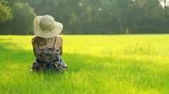 Woman in summer hat sitting on meadow HD Stock Footage