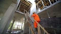 workers carry huge plate by stairs to second storey - stock footage