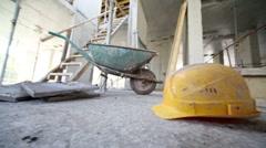 Helmet lies on floor in front of wheelbarrow Stock Footage