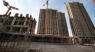Carcass in between unfinished tall buildings and cranes Stock Footage