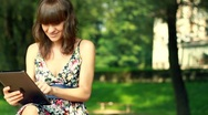 Young happy woman with tablet computer in the park HD Stock Footage
