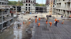 Many builders in action at construction site Stock Footage
