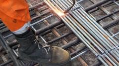 Worker legs weld metal grating by acetylene torch Stock Footage