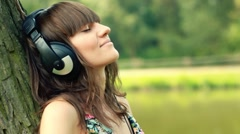 Woman with headphones listen to the music in the park HD - stock footage