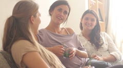 Female friends sitting on sofa drinking tea and chatting - stock footage