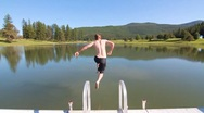 Man jumping into pond slow motion Stock Footage