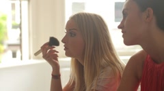 Female friends sitting on bed applying make up and talking Stock Footage