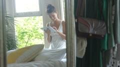 Female sitting in window working on digital tablet Stock Footage