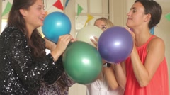 Females friends blowing up balloons at party Stock Footage