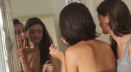 Stock Video Footage of Female friends applying make up in mirror and laughing