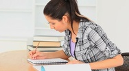 Charming Student sitting at a table learning Stock Footage
