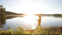 A woman stands angling at a lake at sunset Stock Footage