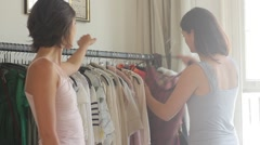 Females friends fitting clothes together in bedroom Stock Footage