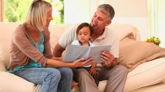 Couple showing book to kid Stock Footage