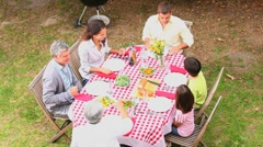 Three generation family eating outdoors - stock footage