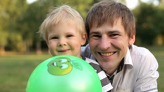 Father and son smiling and looking into the camera - stock footage