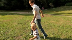 Father and son running on meadow - stock footage