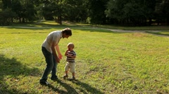 the little boy felt dizzy after spinning at the hands of his dad - stock footage