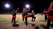 Stock Video Footage of Dolly shot fo high school football cheerleaders kicking.